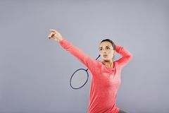 Beautiful young female playing badminton. On grey background. Attractive caucasian woman badminton player with lots of copyspace Stock Photography