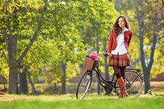 Beautiful young female posing in park with a bicycle Royalty Free Stock Photos