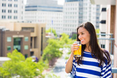 Beautiful young female relaxing on a balcony on a sunny summer day, drinking orange juice Royalty Free Stock Photo