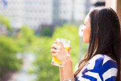 Beautiful young female relaxing on a balcony on a sunny summer day, drinking orange juice Stock Photos