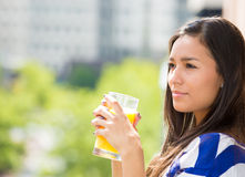 Beautiful young female relaxing on a balcony on a sunny summer day, drinking orange juice Royalty Free Stock Photography