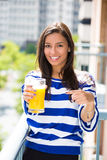 Beautiful young female relaxing on a balcony on a sunny summer day, drinking orange juice Stock Photography