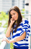 Beautiful young female relaxing on a balcony on a sunny summer day, in her new apartment Stock Photos