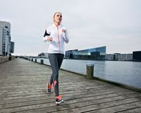 Beautiful young female running on the boardwalk Stock Photography