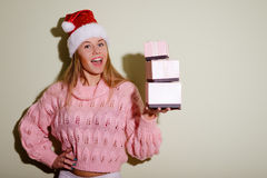 Beautiful young female in Santa hat holding three Royalty Free Stock Images