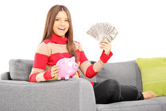 Beautiful young female seated on a sofa holding a piggybank and Stock Image