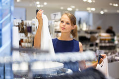 Beautiful young female shopper in a clothing store Royalty Free Stock Image