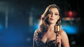 Beautiful young female singer in shiny black evening dress singing with emotions behind microphone at nightclub