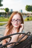 Beautiful young female sitting on the bench in Stock Images