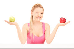 Beautiful young female sitting and holding apples in both hands Royalty Free Stock Image