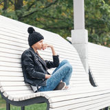 Beautiful young female sitting on a park bench Stock Image