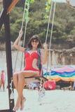 Beautiful young female sitting on the swing on sea shore. Bali island, Indonesia. Pandawa beach. Stock Photos
