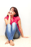 Beautiful young female sitting by the wall Royalty Free Stock Image