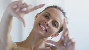Cheerful woman making frame gesture. Beautiful young female smiling and looking at camera while standing on white background and making frame gesture with hands stock footage