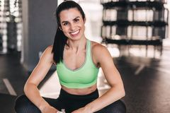 Cheerful woman sitting in gym stock photos