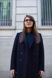 Beautiful young female student in a dark coat standing near office Stock Photo