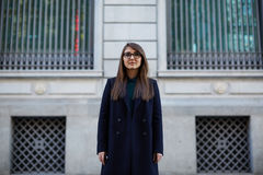 Beautiful young female student in a dark coat standing near office Stock Photos