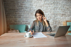 Beautiful young female student fills out the test while having lunch in the cafe. Businesswoman talking on cell telephone while sitting front of open net-book Royalty Free Stock Photos