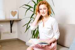 Beautiful young female student with long red hair in a pink skirt and shirt reading a book, holding in her hand a textbook sitting. On the sofa at home, in a Stock Image