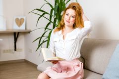 Beautiful young female student with long red hair in a pink skirt and shirt reading a book, holding in her hand a textbook sitting royalty free stock images