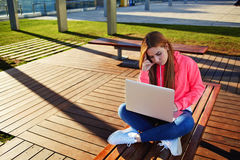 Beautiful young female student sitting on a bench in a computer in the campus Stock Photography