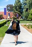 Happy college graduate in tradional attire. Beautiful young female student walking through campus in her gown while flying mortar board hat off to the side royalty free stock images