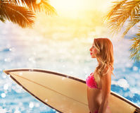 Beautiful young female with surfboard in bikini in a tropical beach. Beautiful young female with surfboard walking in bikini in a tropical beach Stock Images