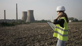 Beautiful young female technician specialist examining power plant area and taking note on clipboard -. Beautiful young female technician specialist examining stock video