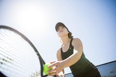 Tennis player reading to serve. Beautiful young female tennis player holding racket and ball in hands, reading to serve Stock Image