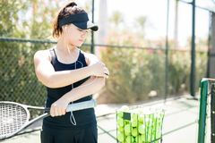 Tennis player turning off the music after practice. Beautiful young female tennis player turning off the music on smartphone mounted on her armband after her Stock Image