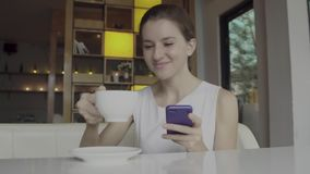 Beautiful young female using smartphone. And smiling stock footage