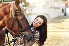 Beautiful young female walking and caressing her brown horse in a countryside.  Royalty Free Stock Photo