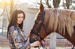 Beautiful young female walking and caressing her brown horse in a countryside.  Royalty Free Stock Photos