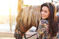 Beautiful young female walking and caressing her brown horse in a countryside Royalty Free Stock Images