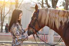 Beautiful young female walking and caressing her brown horse in a countryside Royalty Free Stock Image