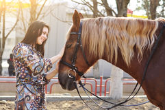 Beautiful young female walking and caressing her brown horse in a countryside Royalty Free Stock Photo