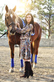 Beautiful young female walking and caressing her brown horse in a countryside.  Royalty Free Stock Image