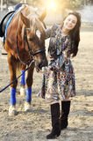 Beautiful young female walking and caressing her brown horse in a countryside Royalty Free Stock Photos