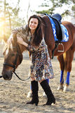 Beautiful young female walking and caressing her brown horse in a countryside.  Royalty Free Stock Images