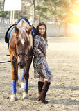Beautiful young female walking with her brown horse in a countryside.  Royalty Free Stock Photos