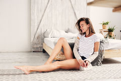 Beautiful young feminine woman relaxing in bedroom in lazy weekend morning, wearing casual fashion. Clothes stock image