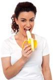 Beautiful young fit girl eating banana Stock Photography
