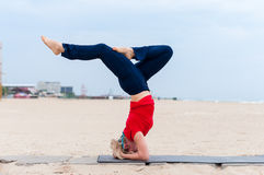 Beautiful young fit woman doing sport exercises, variation of supported headstand posture, salamba sirsasana, side view. Coast on gray background Royalty Free Stock Photography