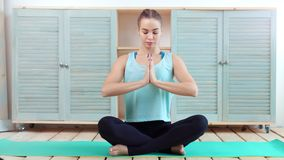 Beautiful young fit woman meditating sitting in lotus pose with closed eyes full shot. Concentration female practicing yoga on mat at home interior making body stock video footage