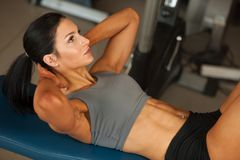 Beautiful young fit woman workout abdominal muscles abs in fitne Stock Images
