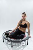 Beautiful young fitness-girl sitting on rebounder Stock Image