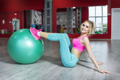 Beautiful young fitness girl trains on fitball Royalty Free Stock Photo