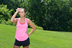 Beautiful young fitness model outside. Beautiful young Caucasian woman in workout gear pauses from outdoor work-out. Looking miserable as she holds a bottle of stock image