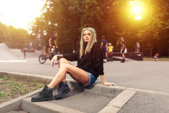 Beautiful young fitness woman in black hoodie sitting near the skate park. Beautiful blonde young fitness woman with dreadlook in black hoodie and Short denim Stock Photography