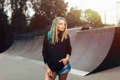 Beautiful young fitness woman in black hoodie standing skate park. Beautiful young fitness woman with dreadlook in black hoodie and Short denim shorts standing Royalty Free Stock Photo